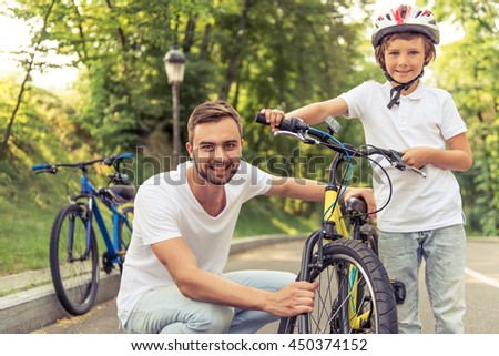 Handsome young dad and his cute little son are riding bikes in park, looking at camera and smiling. Father is examining his son's bicycle - stock photo