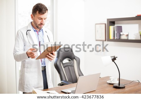 Handsome young doctor with a lab coat and stethoscope reading a patient's history while standing in his office - stock photo