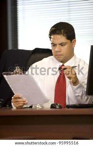 Handsome young executive male working at his desk. - stock photo
