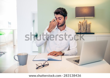Handsome young exhausted businessman working from home with a laptop with his coffee mug