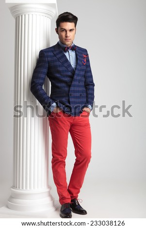 Handsome young fashion man posing with his hands in pockets near a white column on studio background. - stock photo