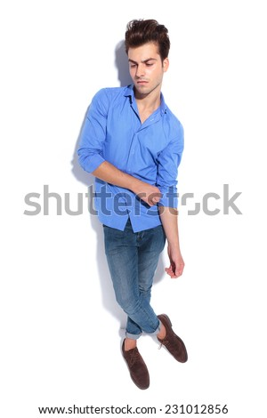 Handsome young fashion man pulling his sleeve while looking down, full body image. - stock photo