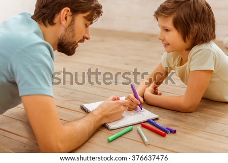 Handsome young father and his cute little son drawing while lying on a wooden floor in the room - stock photo