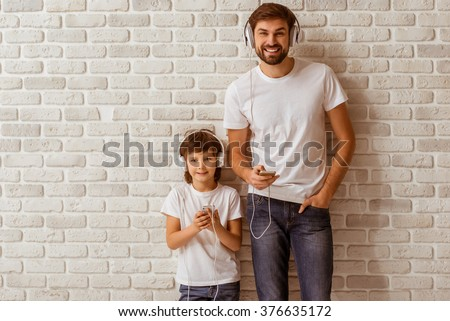 Handsome young father and his cute little son using smart phones, listening to music, looking in camera and smiling. Both in white t-shirts and jeans, standing against white brick wall. - stock photo