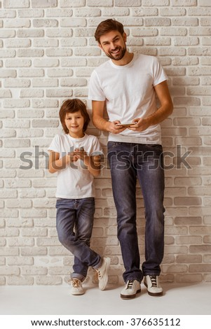 Handsome young father and his cute little son using smart phones, looking in camera and smiling. Both in white t-shirts and jeans, standing against white brick wall. - stock photo