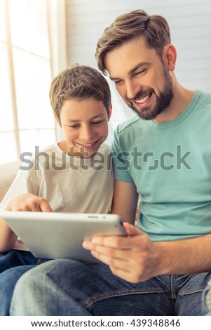 Handsome young father and his son are using a tablet and smiling, sitting on sofa at home
