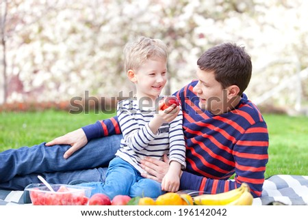 handsome young father and his son having fun together at the picnic - stock photo