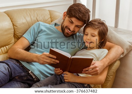 Handsome young father in casual clothes and his cute little son reading a book while lying on a sofa in the room - stock photo