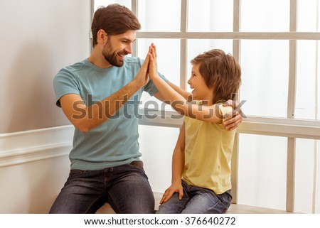 Handsome young father in casual clothes giving a high five to his cute little son while sitting near the window - stock photo