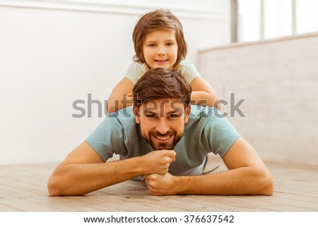 Handsome young father in casual clothes smiling and lying on a wooden floor in the room, his cute little son lying on him - stock photo