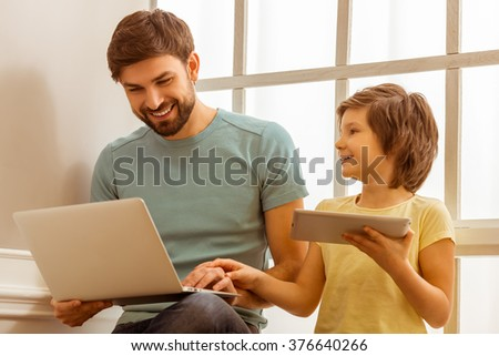 Handsome young father in casual clothes using a laptop and his cute little son using a tablet while sitting near the window - stock photo