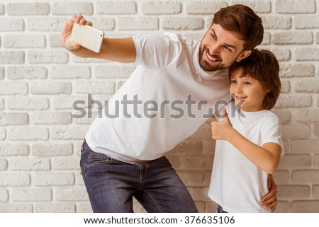 Handsome young father making a photo with his cute little son. A little boy showing OK sign. Both in white t-shirts smiling, standing against white brick wall. - stock photo
