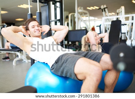 Handsome Young Fit Guy Smiling at the Camera While Doing Sit-ups on Exercise Ball Inside the Gym.