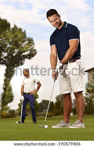 Handsome young golfer ready for holing on the green. - stock photo