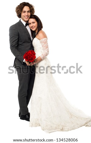 Handsome young groom embracing his wife, full length on white. - stock photo