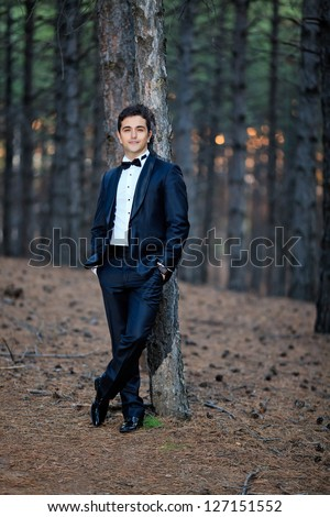 handsome young groom portrait at the forest - stock photo