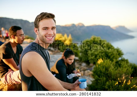 Handsome young guy enjoying a morning cup of coffee with friends on a nature hike - stock photo