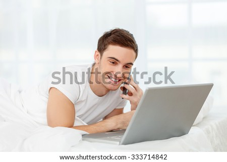 Handsome young guy is talking at the mobile mope in the morning. He is lying on bed and looking at laptop. The guy is smiling happily - stock photo