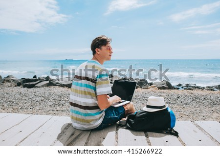handsome young guy the photographer working with a laptop on the beach