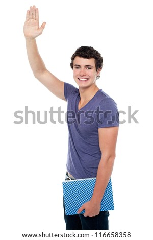Handsome young guy with a notebook in hand putting his right hand up isolated over white