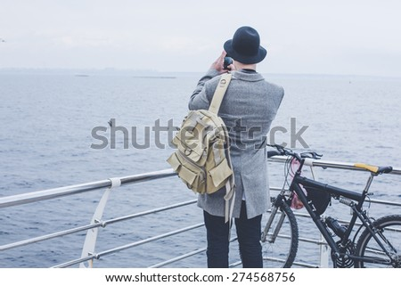 handsome young hipster guy in hat with bike taking picture of the sea with his smart phone wearing backpack on wood floor back view - stock photo