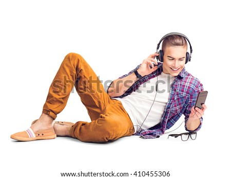 Handsome young hipster man lying on the floor listening to music with smart phone. Handsome young stylish man in headphones with smartphone, isolated on a white background - stock photo