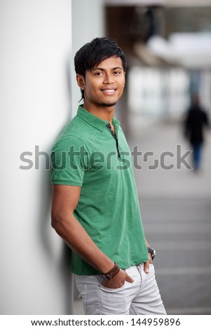 Handsome young indian man leaning against wall - stock photo