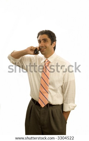 Handsome young Iranian businessman with hand in pocket and on cell phone