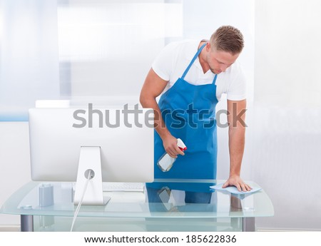 Handsome young janitor or cleaner cleaning an office spraying the top of the desk with disinfectant before the office workers start their day - stock photo