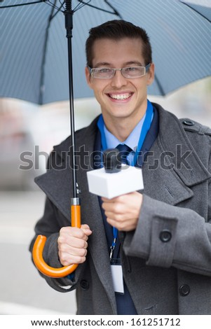handsome young journalist working outdoors in the rain - stock photo