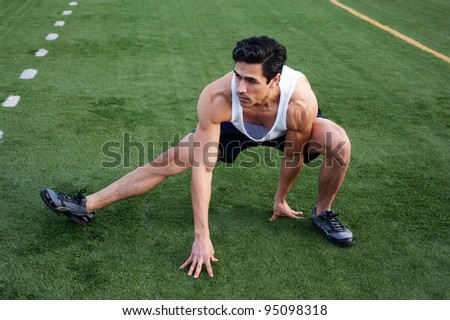 Handsome, young latino athlete stretching