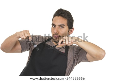 handsome young male chef wearing black apron holding fork and knife isolated on white - stock photo