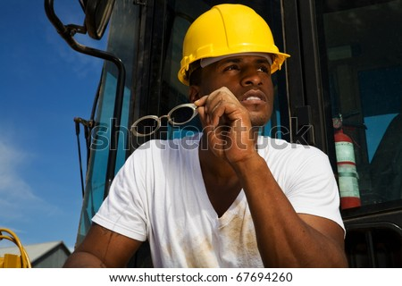 handsome young male construction worker wearing a hard hat, white t-shirt and jeans working beside his tractor rig - stock photo