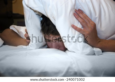 Handsome young male insomniac covering his head and ears trying to block out the sound with a pillow as he is kept awake by loud noises around him - stock photo
