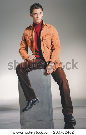 handsome young male model sitting cube - studio shoot - stock photo