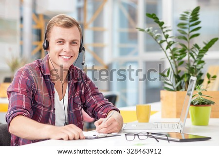 Handsome young male operator is speaking by hands-free. The man is sitting at desk near laptop and writing down notes. He is looking at camera and smiling - stock photo