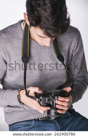Handsome young male photographer looking at photographs on his professional photo camera's display hanging from his neck, isolated on white - stock photo
