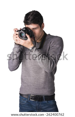 Handsome young male photographer taking photograph with professional photo camera hanging from his neck, isolated on white - stock photo