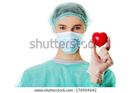 Handsome young male surgeon doctor holding heart shape toy, on white  - stock photo