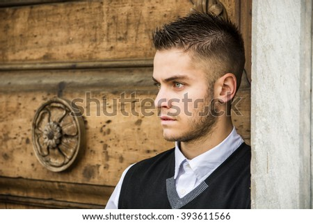 Handsome young man against old wood door - stock photo