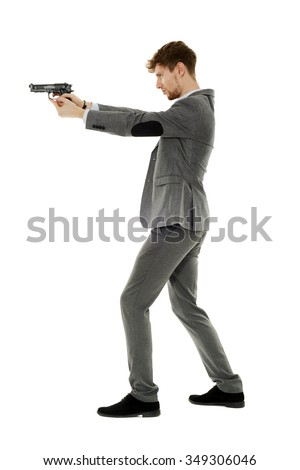 Handsome young man aiming the gun to an invisible target - stock photo