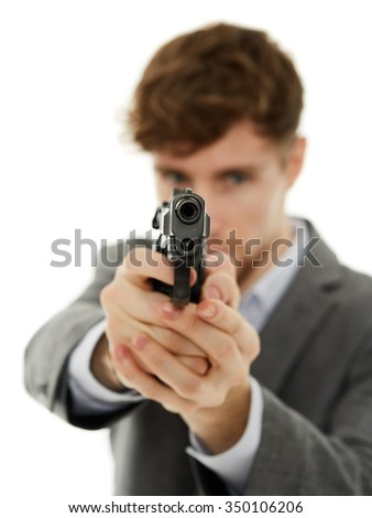 Handsome young man aiming the gun to an invisible target, with selective focus - stock photo