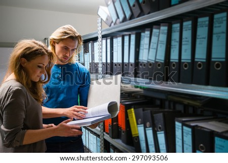 handsome young man and attractive woman checking documents in the company archives - stock photo