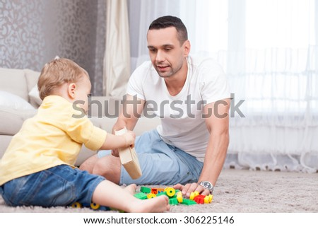 Handsome young man and his son are sitting on flooring and playing with toys. The parent is giving a book to the kid and smiling. The boy is taking it with interest - stock photo