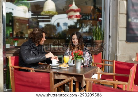 Handsome young man and woman of pleasant appearance are an interesting and pleasant conversation while sitting in sidewalk cafe outdoors on a warm autumn day with cup of coffee and fresh orange juice  - stock photo