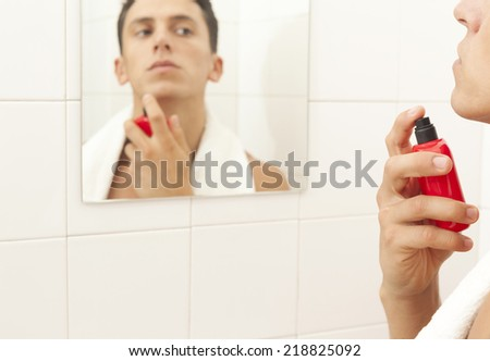 Handsome young man applying parfume at the bathroom - stock photo