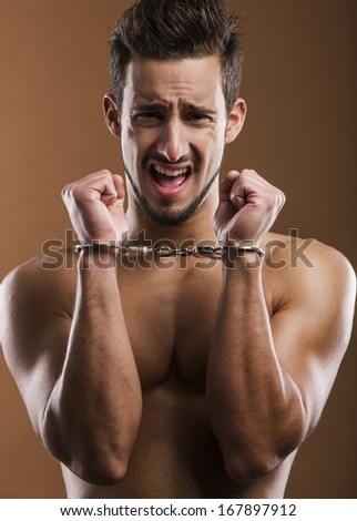 Handsome young man arrested with handcufs on his hands - stock photo