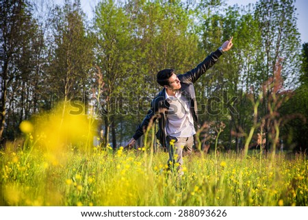 Handsome young man at countryside, touching grass and flowers, standing in  field or grassland, wearing white shirt and jacket, looking down - stock photo