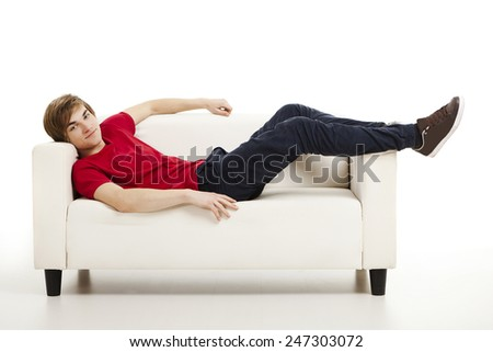 Handsome young man at home lying on the couch