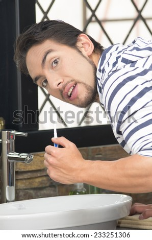 handsome young man brushing his teeth in modern bathroom - stock photo